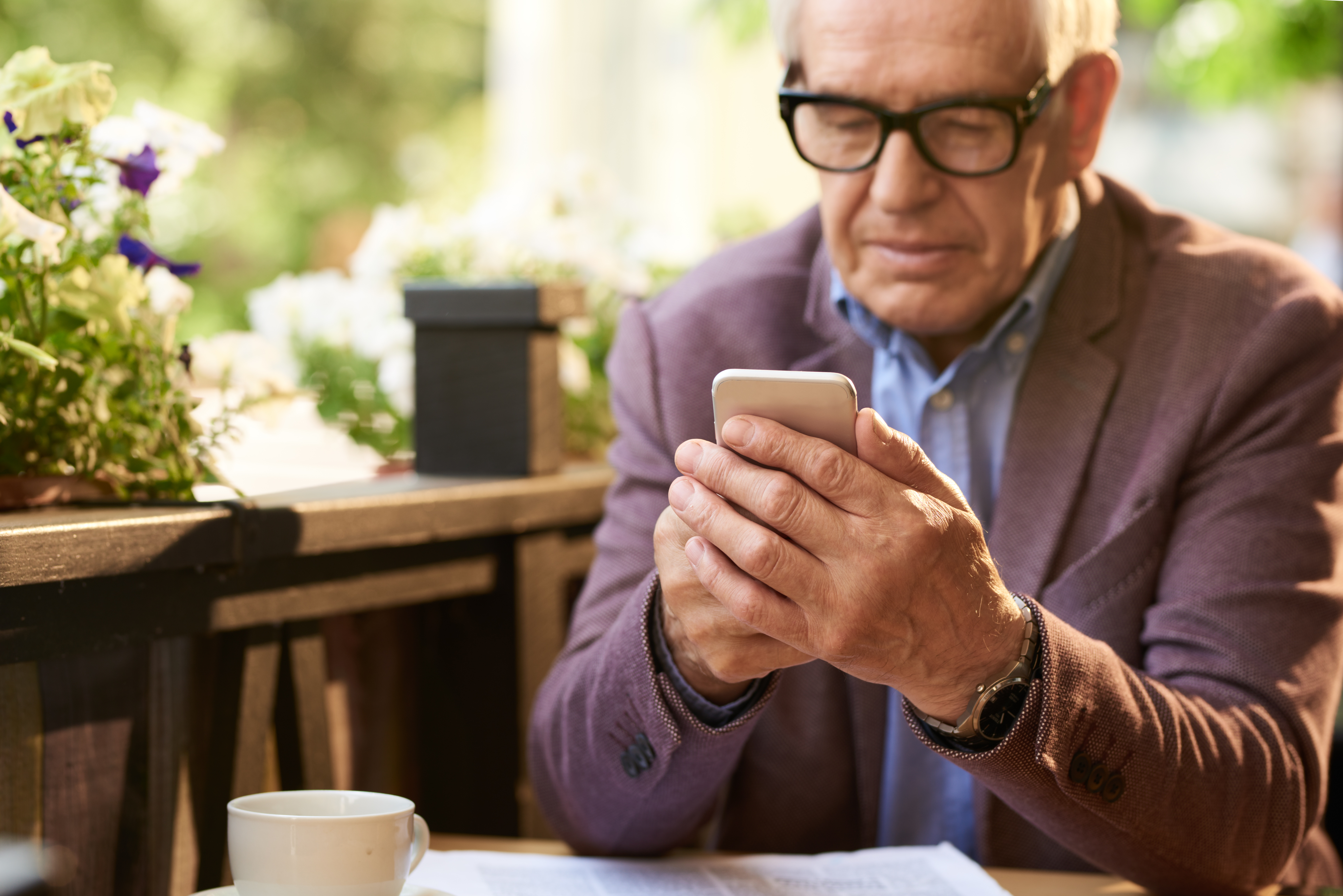Portrait of modern senior man using smartphone in outdoor cafe, typing text messages